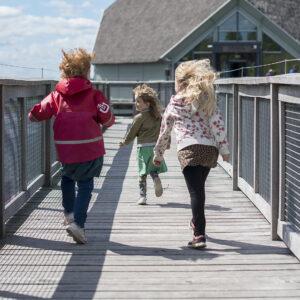 Barn som springer mot naturum. Foto.